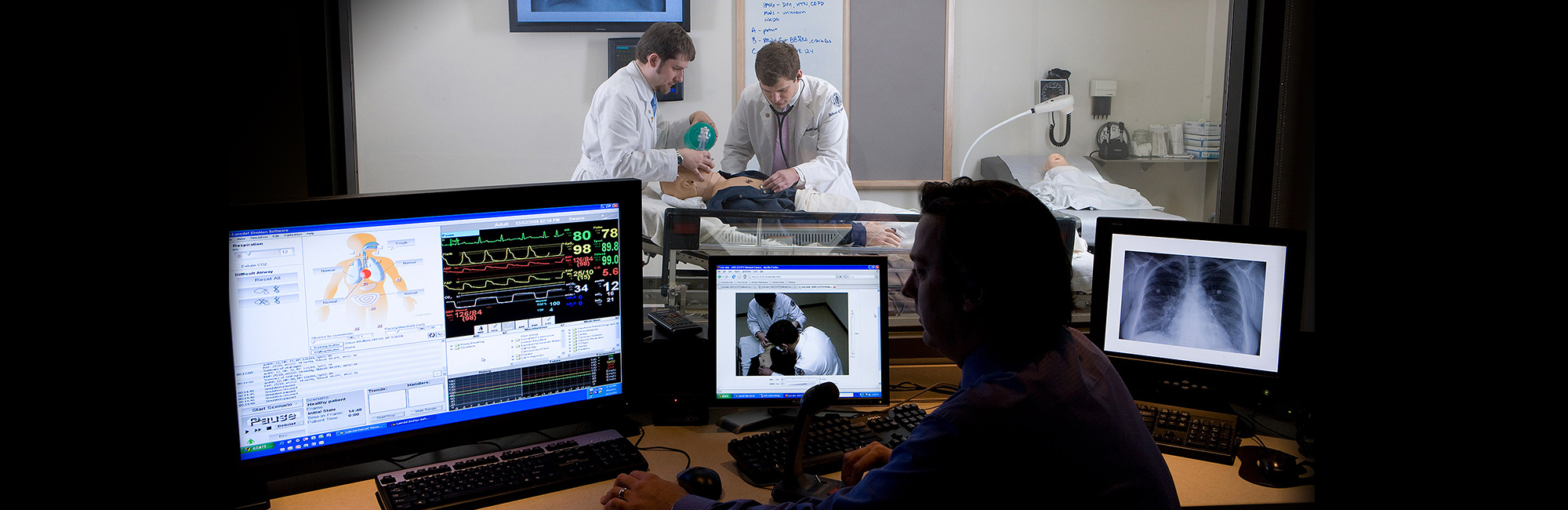 Dr. Thomas Nowicki, director of medical simulation at UConn observes Benjamin Silverberg, a fourth year medical student and Austin Schirmer, a second year medical student