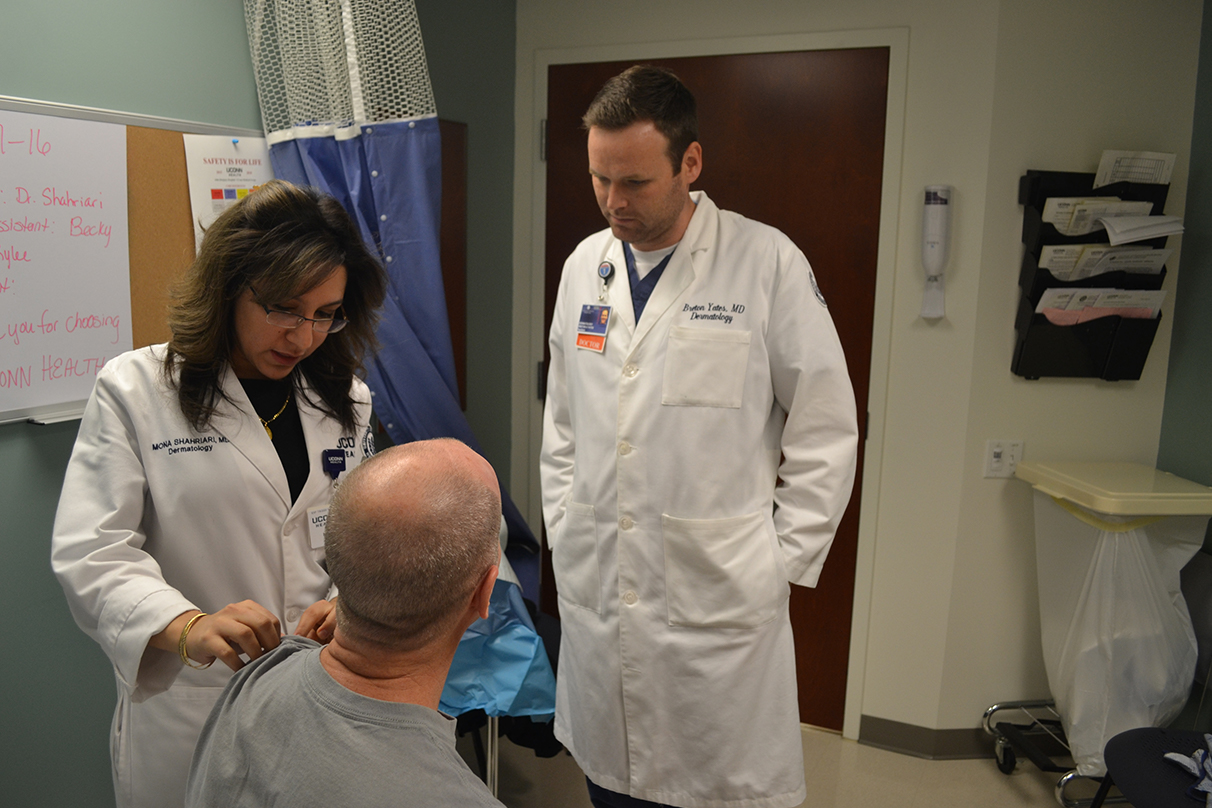Dr. Mona Shahriari and Dr. Breton Yates, chief dermatology resident, see a patient at UConn Health in Canton. (Photo by Chris DeFrancesco)