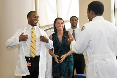 students receiving white coats
