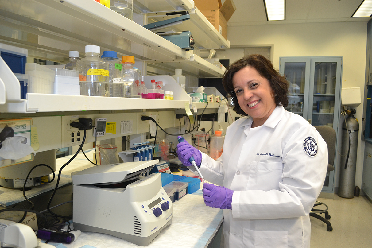Annabelle Rodriguez-Oquendo, a UConn Health research, in her lab holding a pipette and smiling for the camera